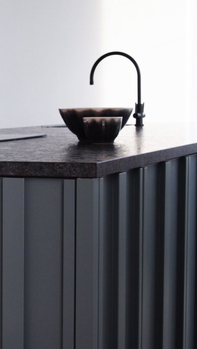 Kitchen detail, bespoke cabinetry, brushed granite surface, black sanitaryware and sink