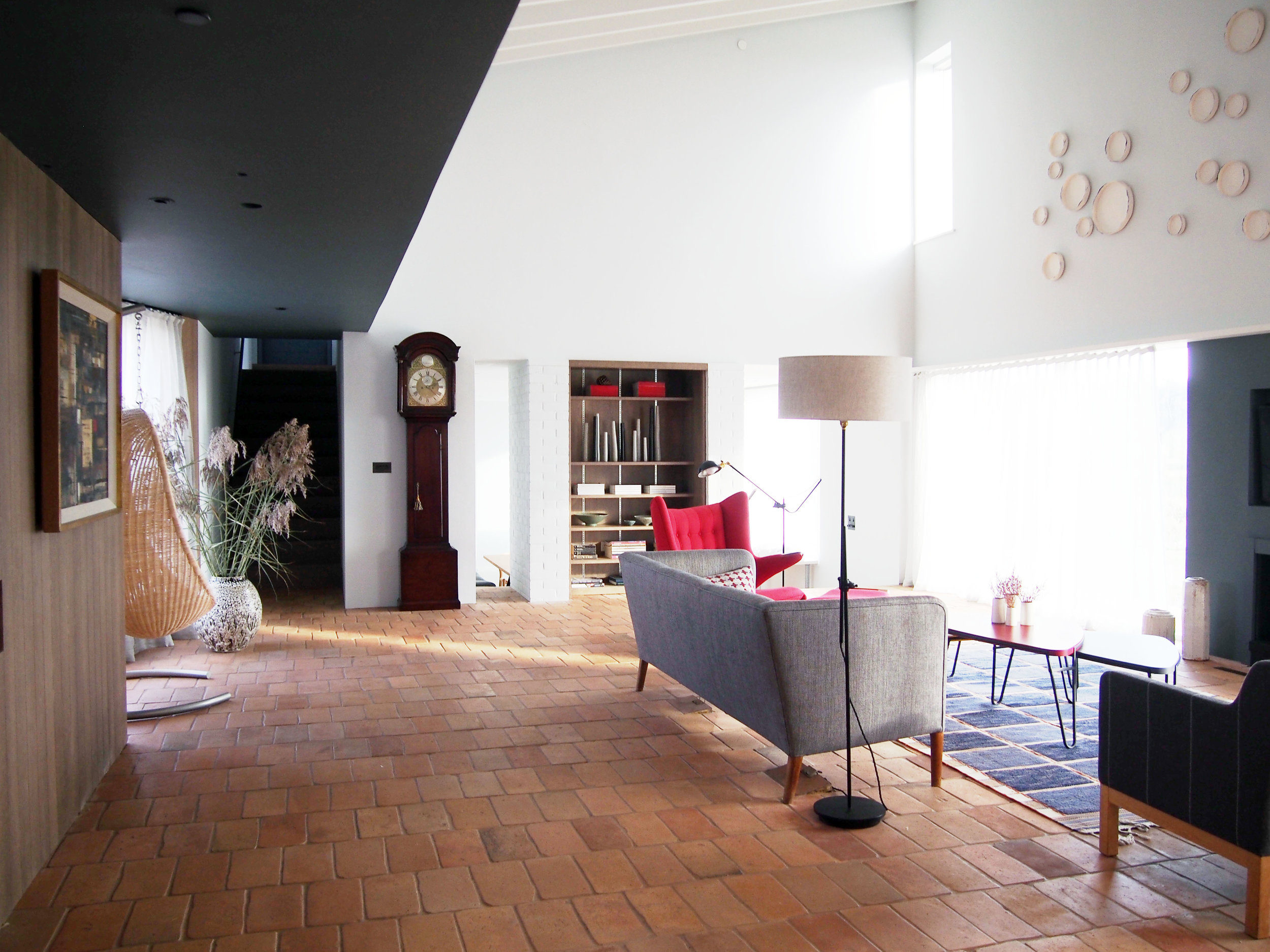 View of the sitting room from entrance area, showing darkened ceiling to enhance the planes of the space, hanging chair, and ceramics by Valeria Nascimento above the fire on the east wall