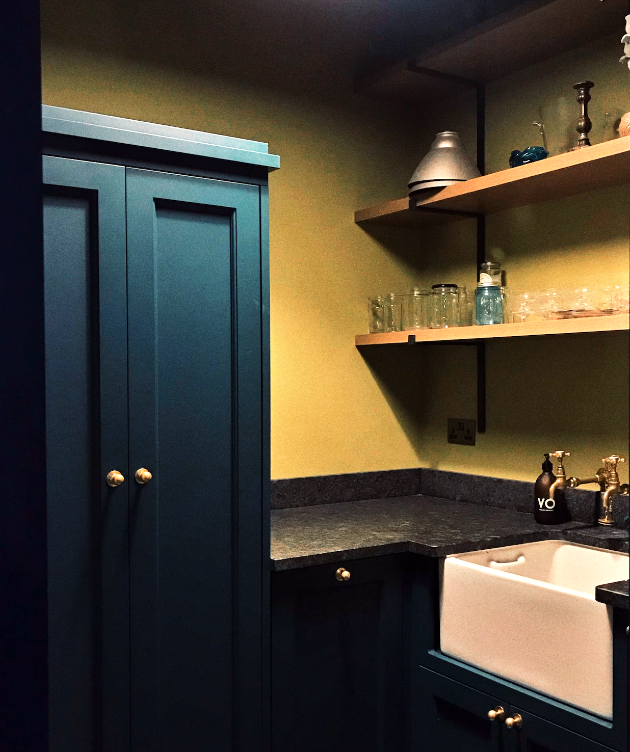 Laundry painted mustard, with dark blue cabinetry, brushed black granite, cabinetry concealing all appliances and storage, with overhead drying racks, butler sink, and shelving for flower vases