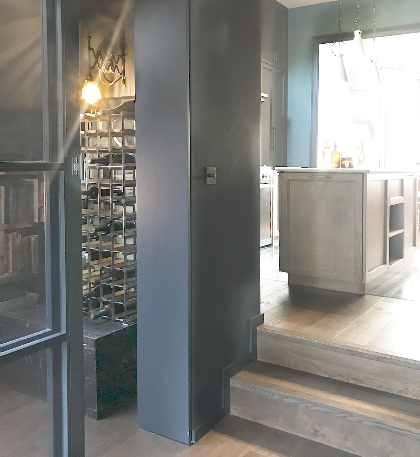 View into pantry, with wine storage, extendable vintage light over, sliding black wood and glass doors, then up wooden steps into kitchen