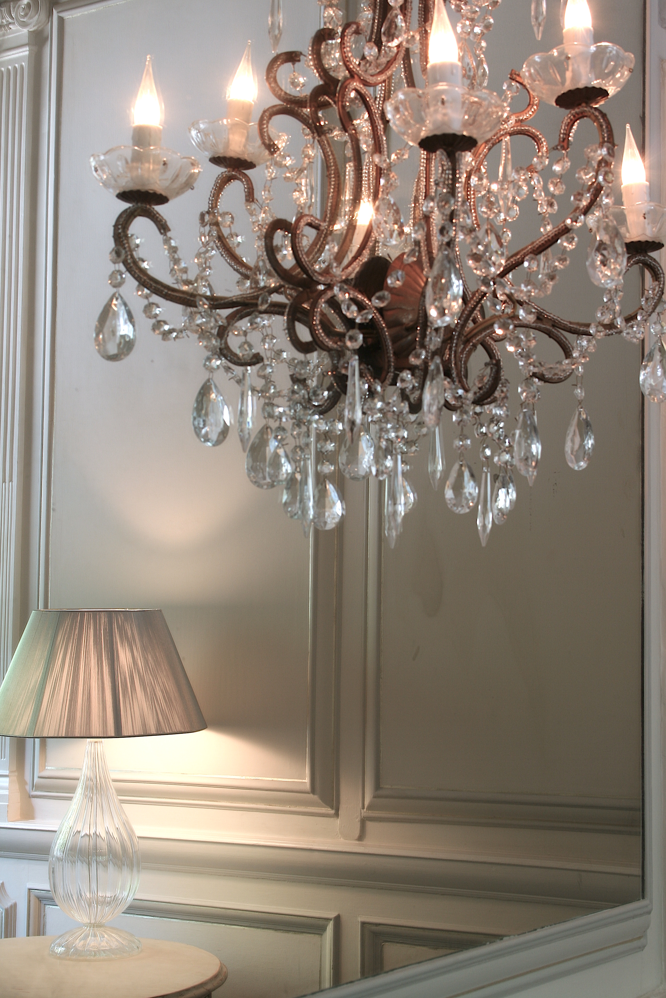 The existing panelling was painted in pale grey, finished with an antique wash, and edged in moon gold, to detail the shapes. Bespoke chandelier sconces were backed onto hand made antique mirror panels, facing the large sash windows