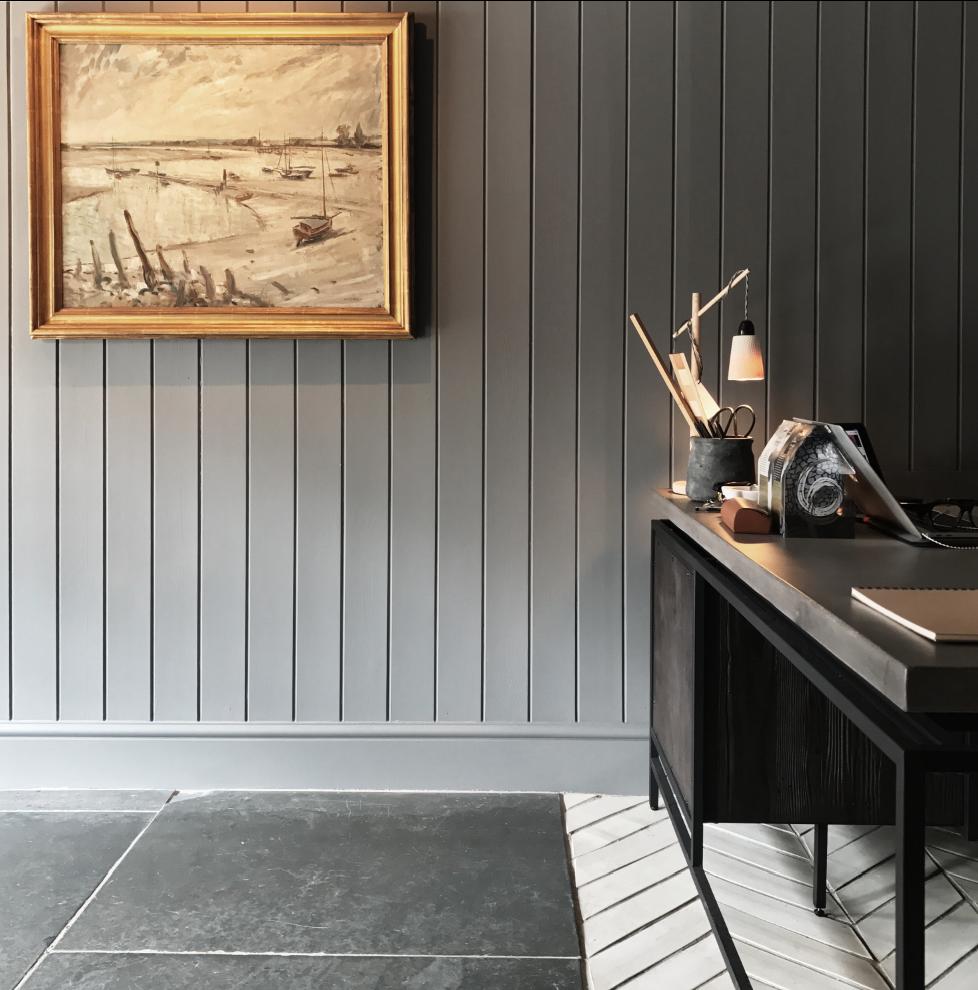 Concrete, blackened steel and cerused oak desk, against grey panelling, and herringbone ceramic and slate floors