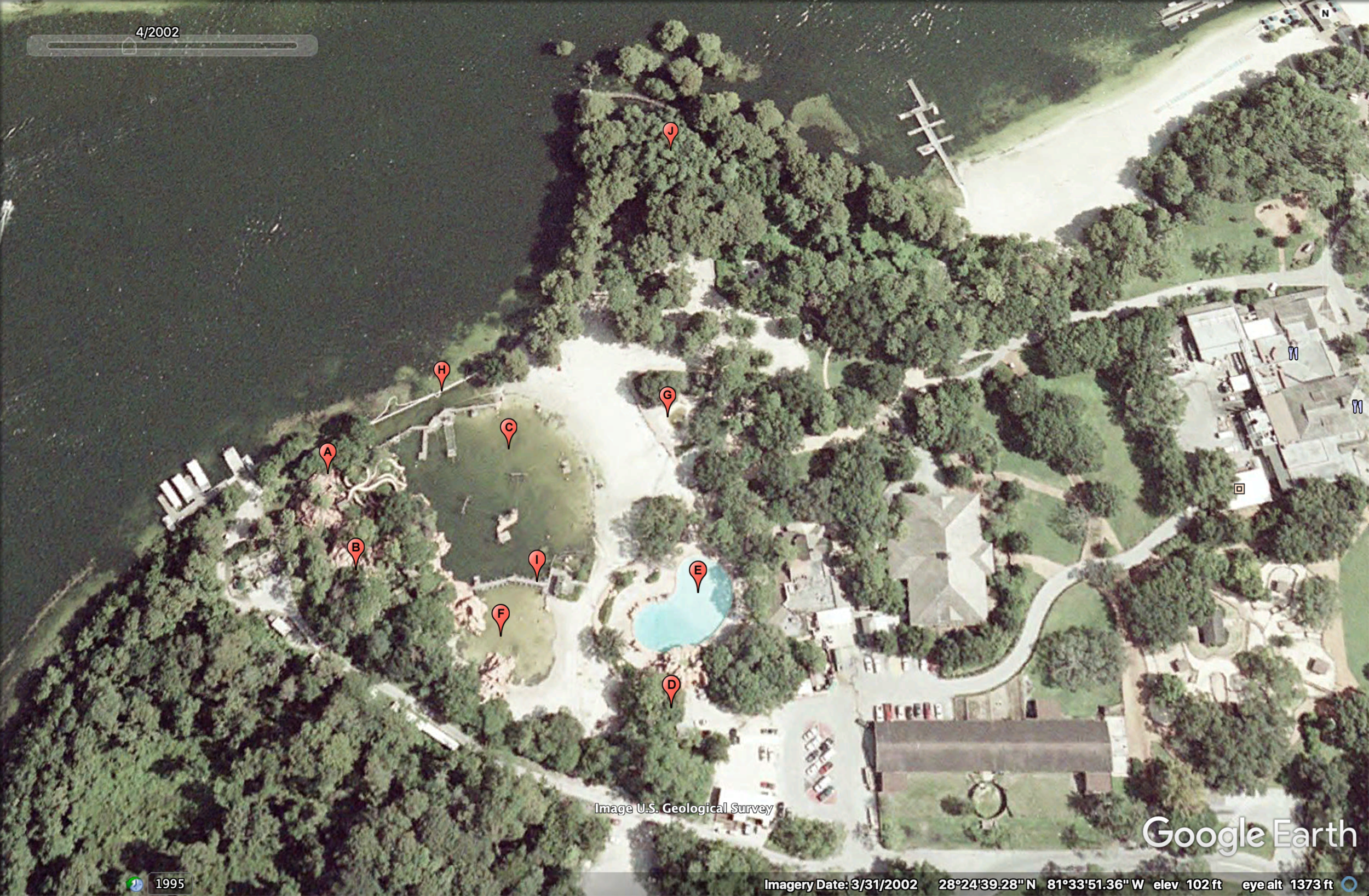 Aerial view of River Country in April 2002 less than a year after its closing. Plants haven't yet begun overrunning the property as they would in the near future. Red pins represent each of the park's attractions. A) Whoop 'n Holler Hollow; B) White Water Rapids; C) Bay Cove Pool; D) Slippery Slide Falls; E) Upspring Plunge; F) Kiddie Kove; G) Indian Springs; H) Bay Bridge; I) Barrel Bridge; J) Cypress Point Nature Trail. (Photo: Google Earth, labeling by me)