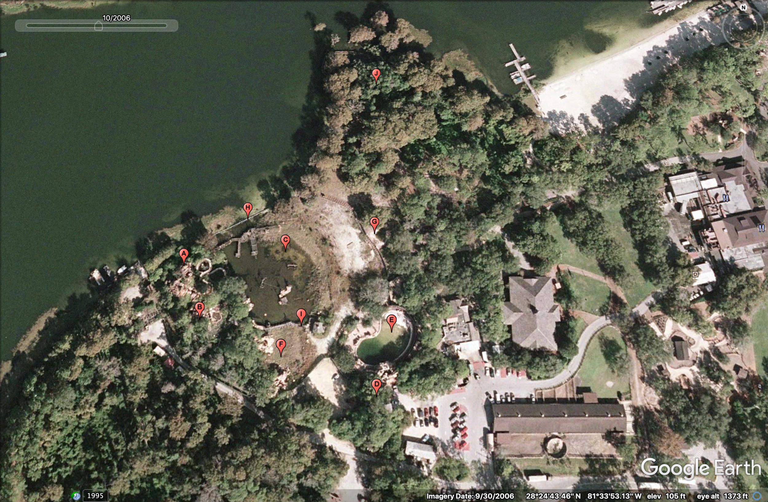 Aerial of River Country in October 2006, nearly five years after closing. Red pins represent each of the park's attractions. A) Whoop 'n Holler Hollow; B) White Water Rapids; C) Bay Cove Pool; D) Slippery Slide Falls; E) Upspring Plunge; F) Kiddie Kove; G) Indian Springs; H) Bay Bridge; I) Barrel Bridge; J) Cypress Point Nature Trail (Photo: Google Earth, labeling by me)