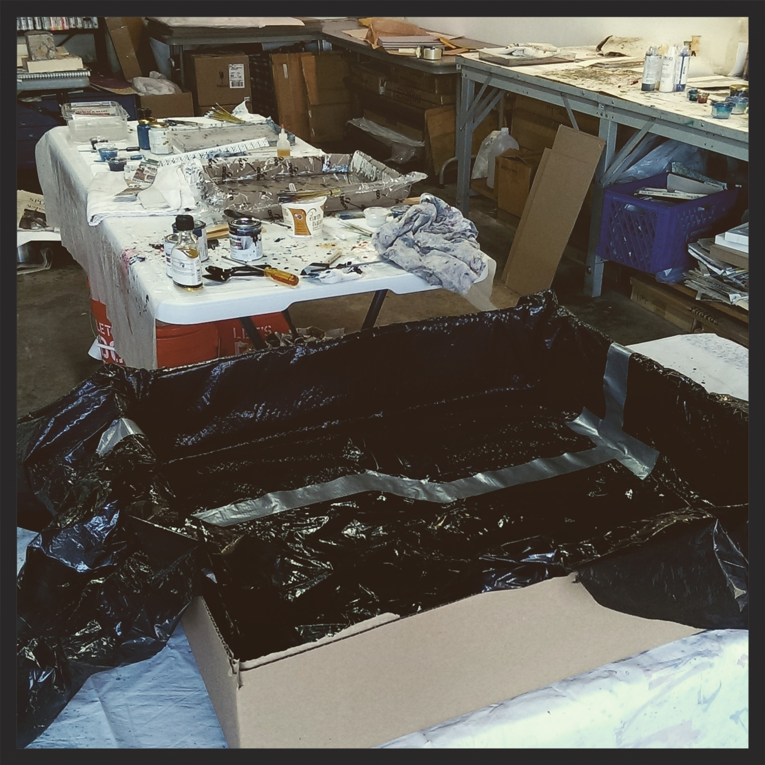 In the foreground is a tank I build from a cardboard box and two trash bags duck-taped together. The tank is the same size that the women artisans use. I wanted to replicate surface space and surface tension as I experimented with paint formulas.