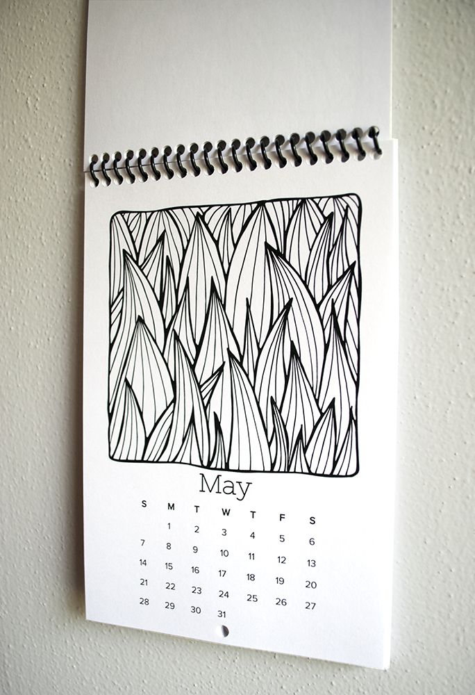The spiral bound calendar comes with a small hole in each page so it's easy to hang.
