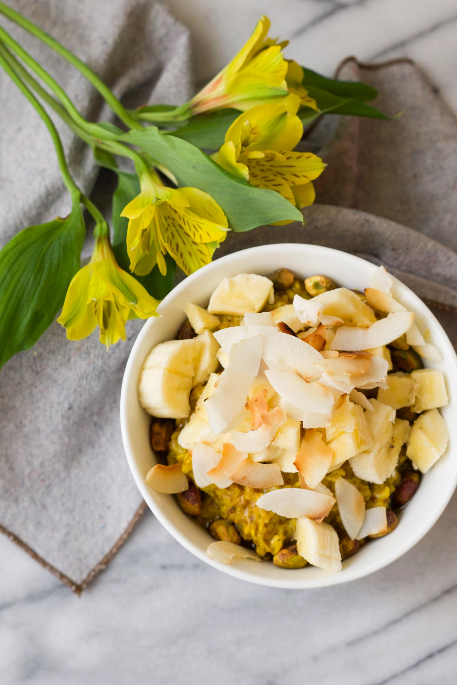 Vegan & Gluten Free Golden Banana Oatmeal topped with banana, pistachios, and toasted coconut chips. by Beautiful Ingredient