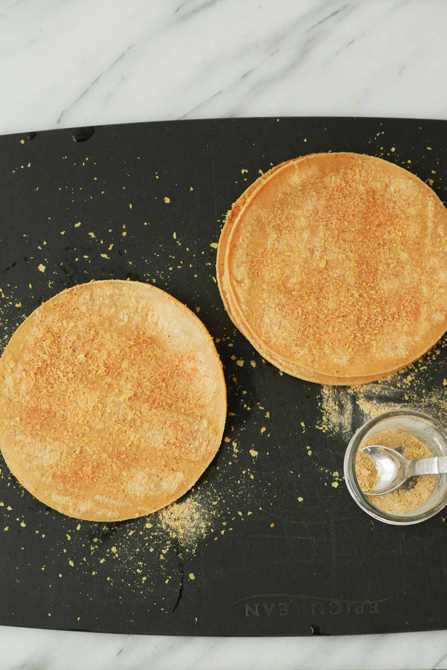 Sprinkling spices on tortillas for chips. By Beautiiful Ingredient