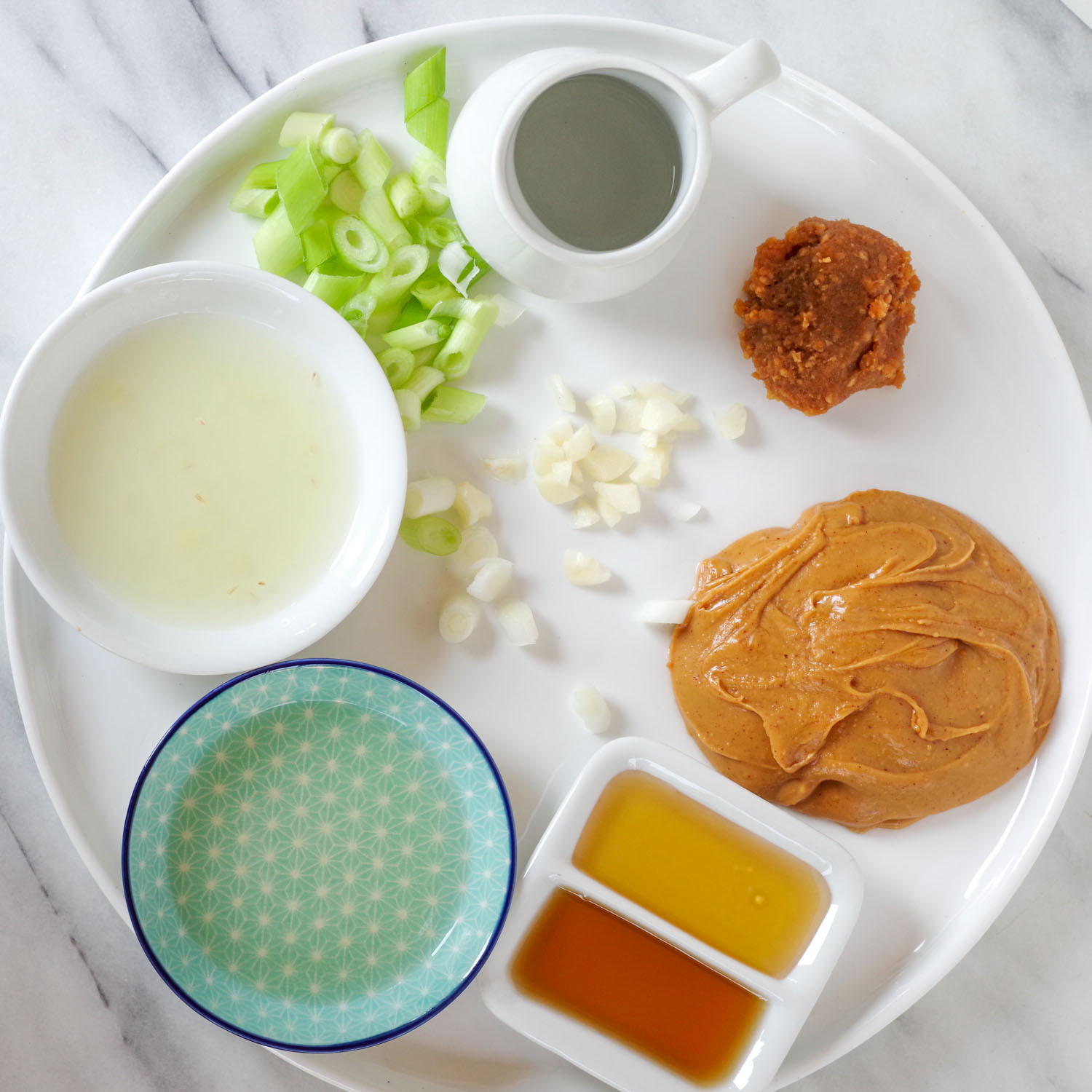 Miso Peanut Drizzle ingredients. clockwise from top: water, red miso paste, peanut butter, agave, sesame oil, rice vinegar, lemon juice, scallions, garlic