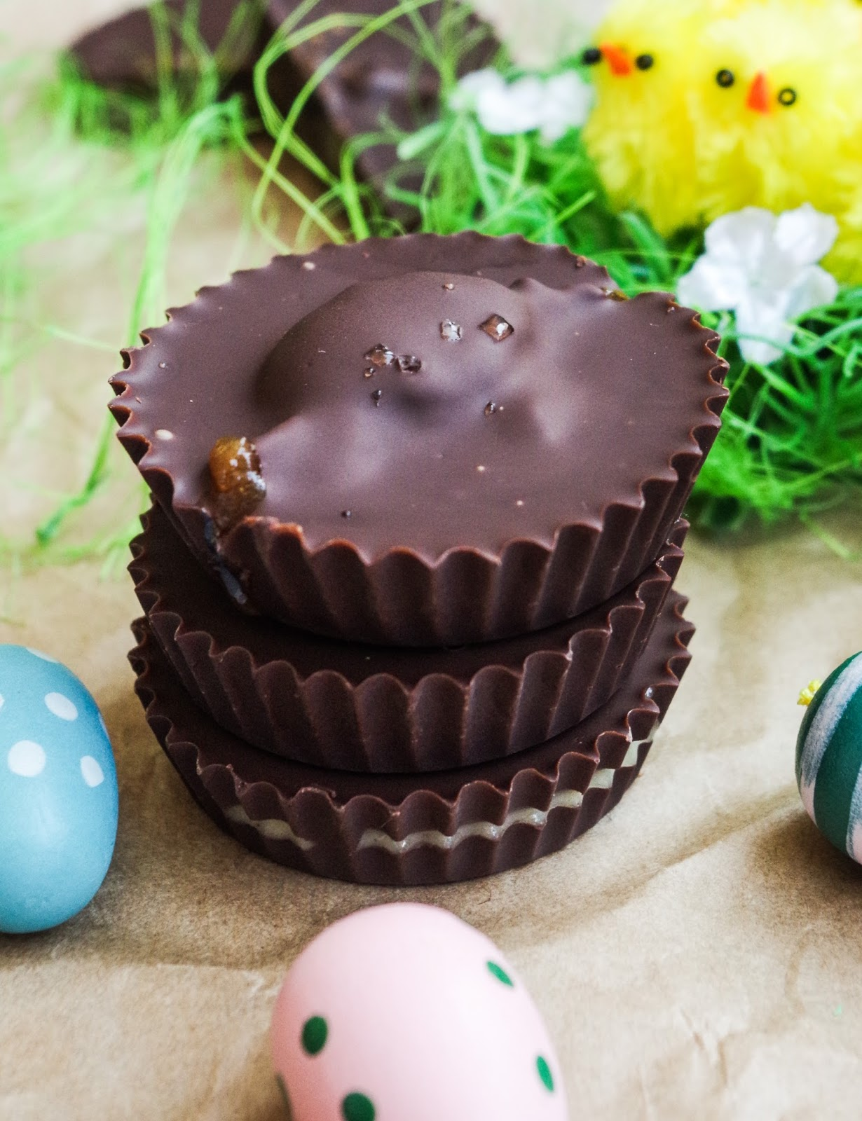 Easter Chocolate Cups in 3 flavors: Salted Vanilla Caramel, Cashew Cream Egg, Hot Cross Bun by Cassidy of Euphoric Vegan. #eastertreats #easter #bunny #rabbit #easterdesserts #veganeaster #veganeasterrecipes #eastergifts #eastervegan #veganeastergifts #homemadeveganeaster