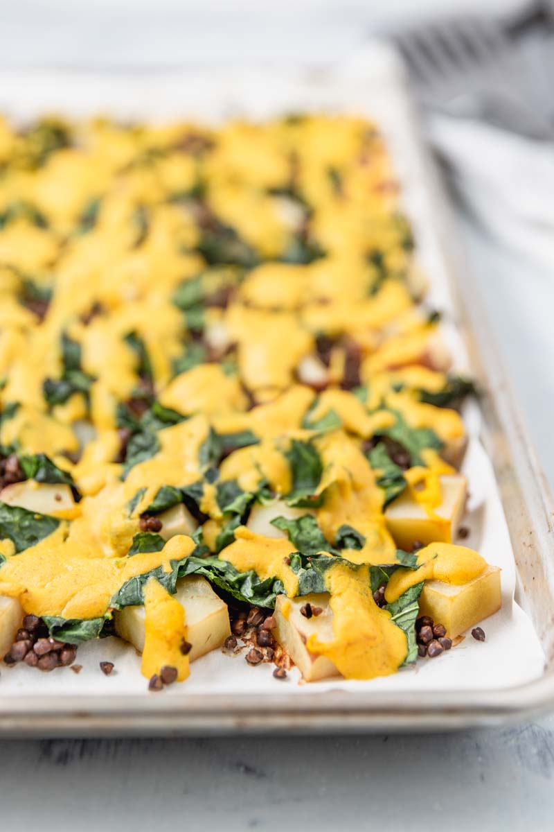 Cheesy Vegan Sheet Pan Potatoes with Greens and Lentils makes a full, satisfying meal. #plantbased #dinner #cheesy #vegan #cheesesauce #wfpb #glutenfree #grainfree #oilfree #greens #kale #collards #lentils #veggies #sheetpan #comfortfood #easter #easterbrunch #veganeaster