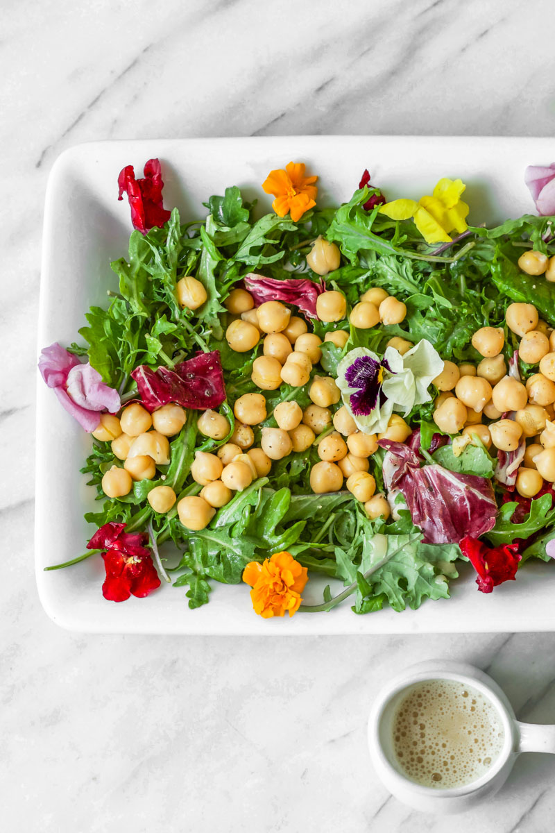 Adding edible flowers to mixed greens and chickpeas is an easy way to create a beautiful spring salad. Then all you need to make is this easy Go-To Oil-Free Salad Dressing. #springsalad #saladdressing #vegan #vegansaladdressing #lemon #lemondressing #oilfree #oilfreedressing #oilfreevegan #oilfreevegandressing #easter #easterbrunch #eastersalad #salad #vegansalad
