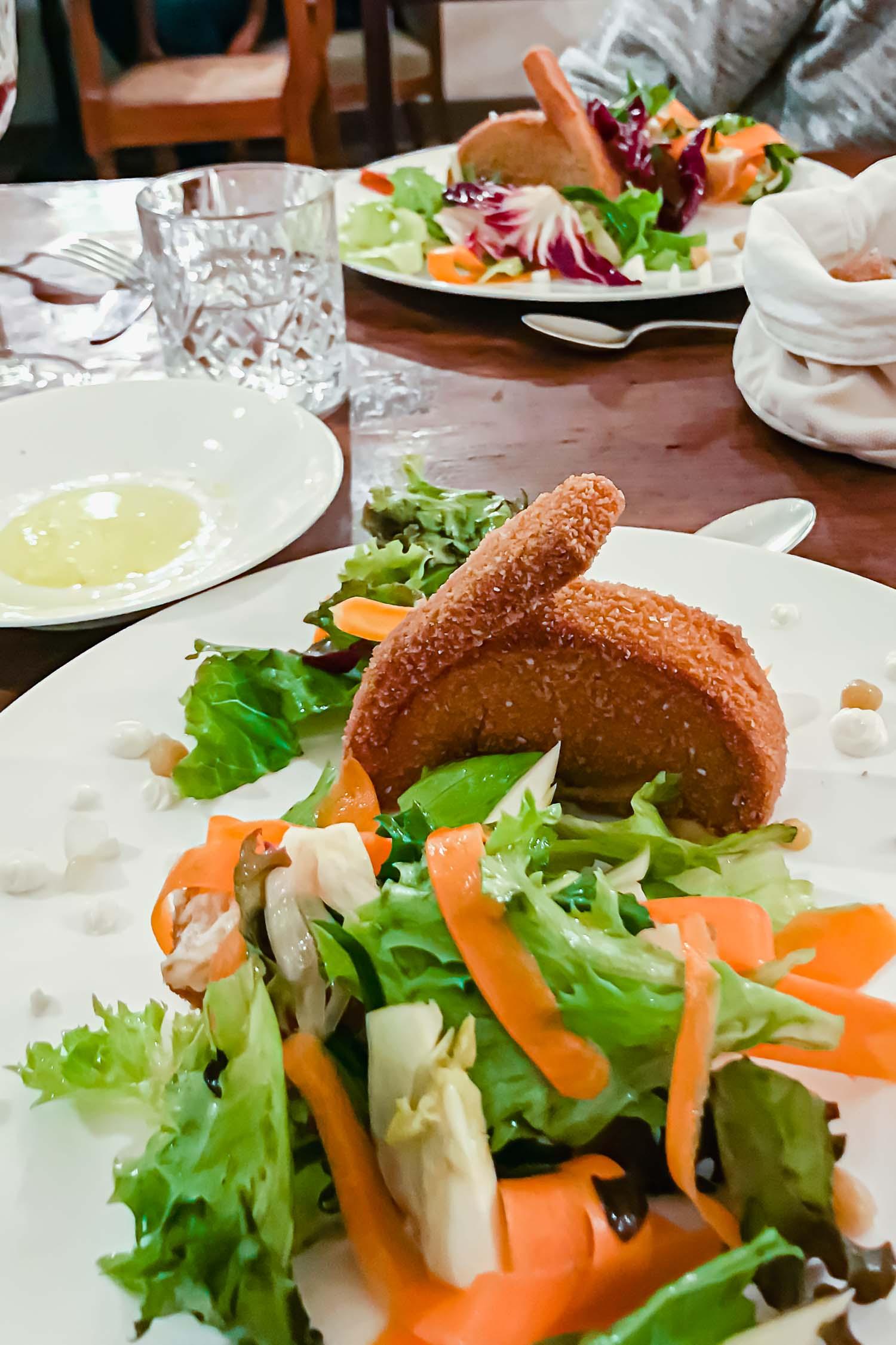 Salad with chickpea fritters shaped like rabbits at the i pini restaurant, an organic vegan Italian farmhouse in Tuscany. #tuscany #travel #italy #italianfarmhouse #olivegroves #oliveoil #vineyards #italyinautumn #veganrestaurant #vegantravel #italytravel #veganitaly #vegantuscany #veganhotel #ecotourism #organichotel #veganhotel #veganretreat #veganbedandbreakfast #sangimignano