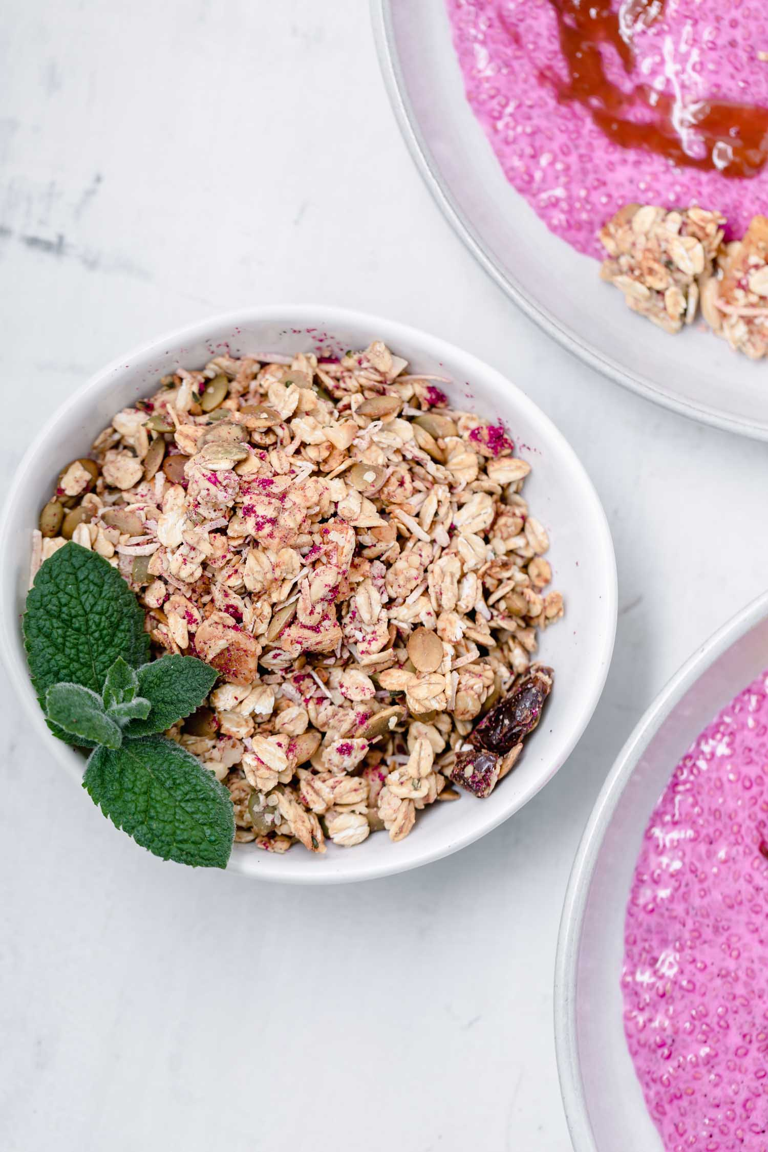 Tropical granola flavored with banana, pineapple, coconut, and macadamia nuts and dusted pink with pitaya (dragon fruit) powder. #tropicalgranola #granolarecipe #summerrecipe #summertime #tropical #tropicalrecipe #vegangranola #veganrecipe #glutenfreevegan #pinkfood