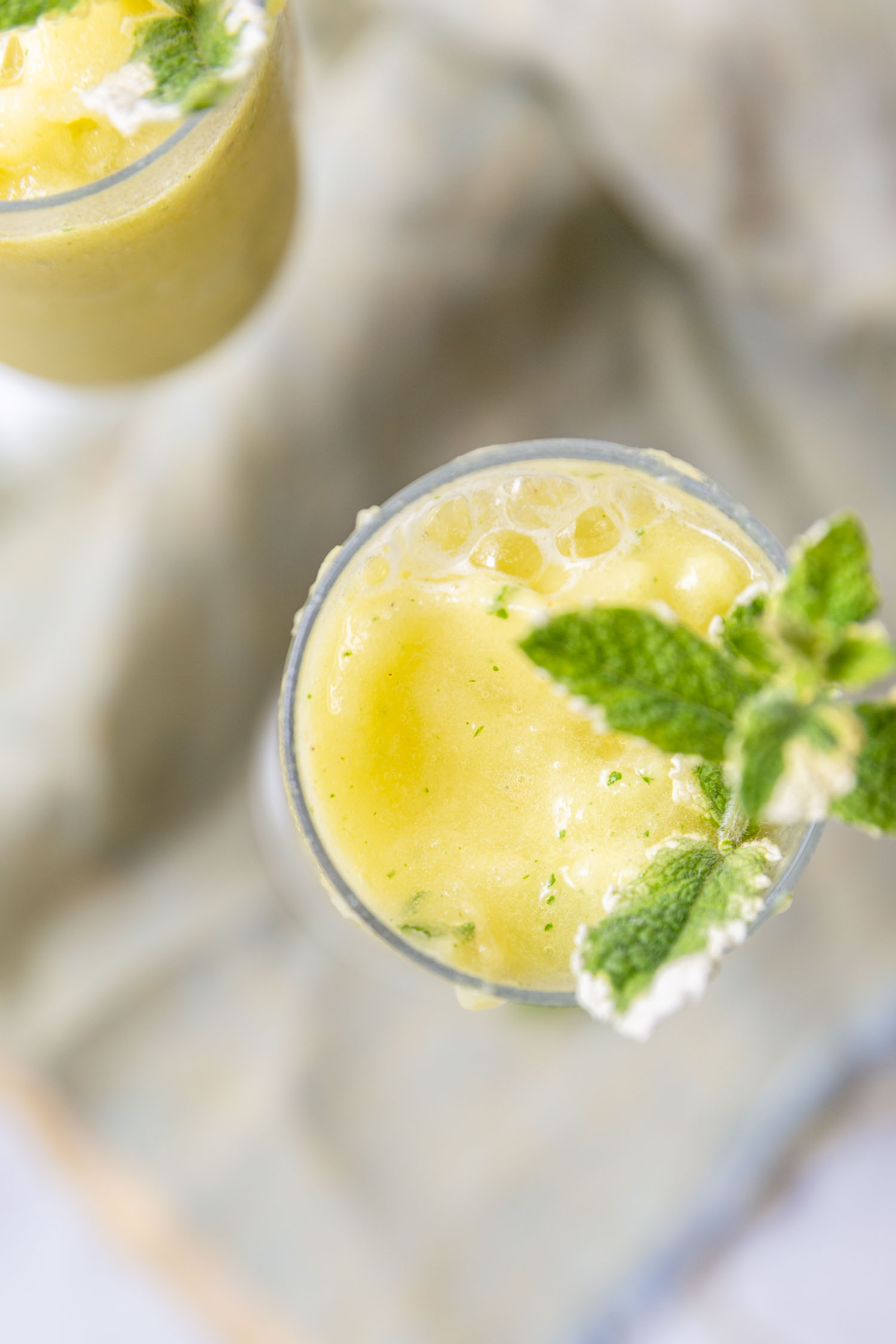 Pineapple Mint Frozen Drinks require just two ingredients (+ water) for a delicious and refreshing mocktail - add your favorite spirits for the ideal summery cocktail. #summerdrink #summercocktail #cocktail #pineapple #pineapplemintrecipe #drinkrecipe #frozendrink #blended #mocktail #fruitydrink #tropicaldrink #mojito