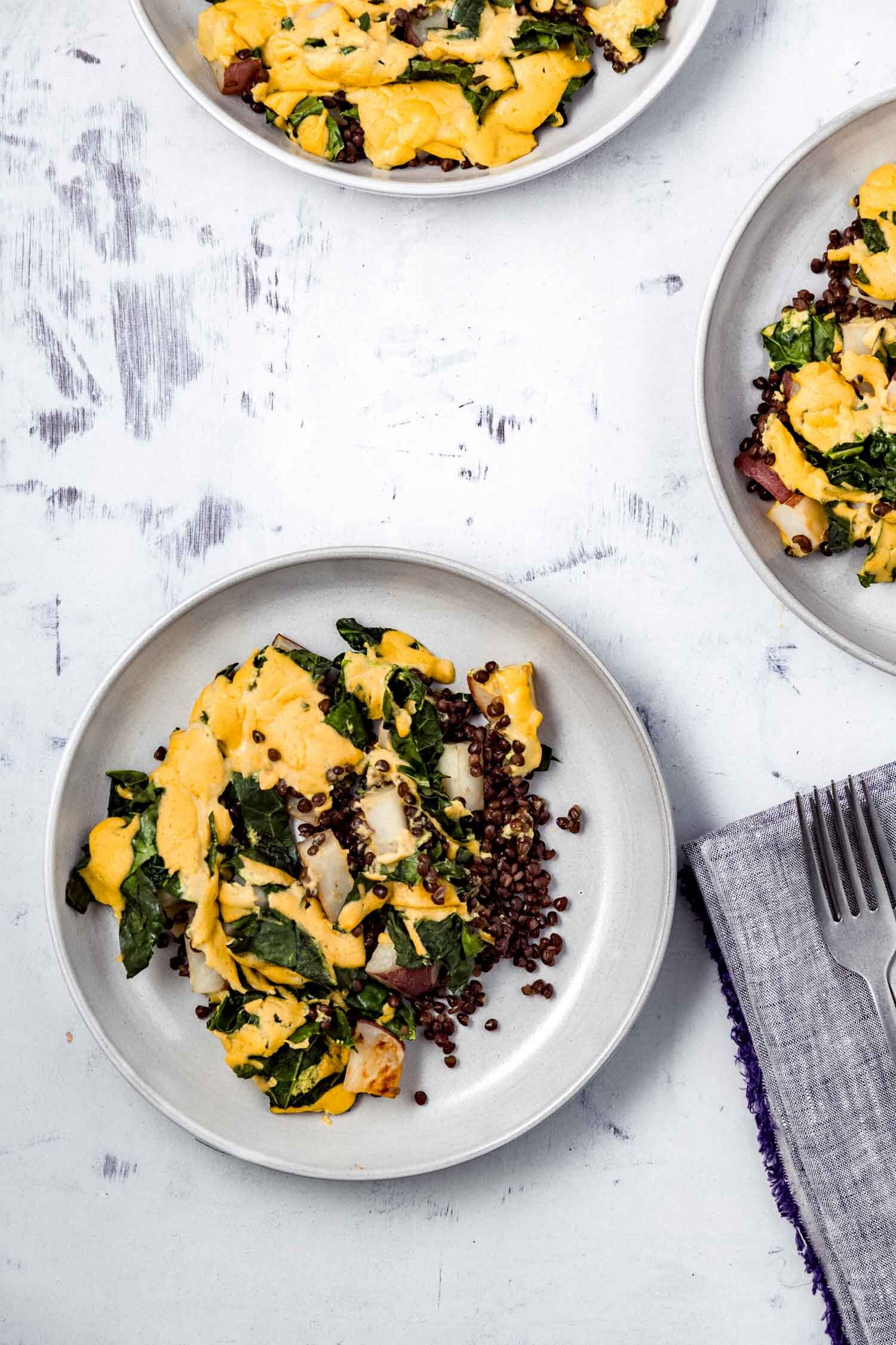 Cheesy Vegan Sheet Pan Potatoes with Greens and Lentils makes a full, satisfying meal. #plantbased #dinner #cheesy #vegan #cheesesauce #wfpb #glutenfree #grainfree #oilfree #greens #kale #collards #lentils #veggies #sheetpan #comfortfood