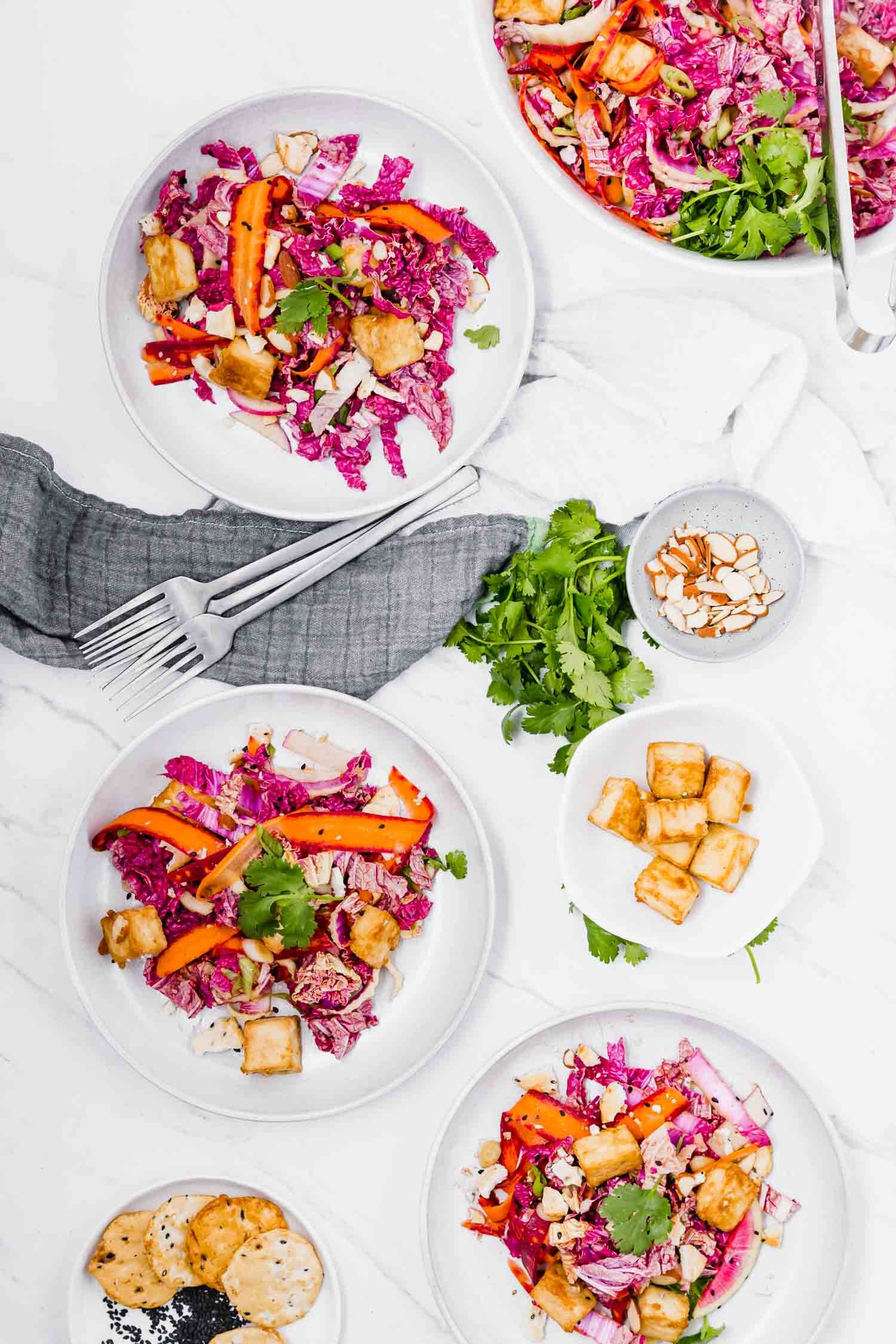 Crisp and Colorful Sesame Tofu Salad is a vegan play on Chinese Chicken Salad, with lots of crunch and flavor. #vegansalad #plantbased #dinner #lunch #salads #asiansalad #chinesechickenlesssalad #meatfree #refinedsugarfree #glutenfree #tofu #bakedtofu #crowdpleaser #ricecracker #colorfulfood