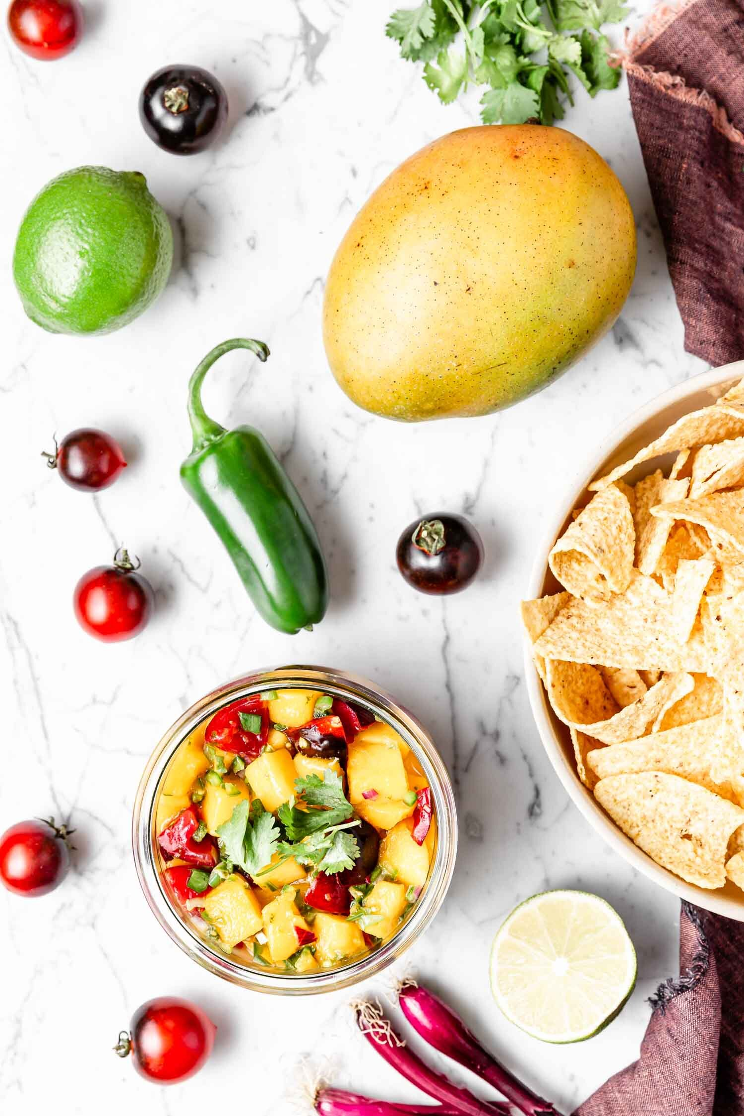 5-ingredient Mango Salsa that is fresh, vibrant, and full of flavor - plus, it's ready in just a few minutes! Sure to disappear quickly, so make a big batch! Recipe by Kari of Beautiful Ingredient.  #mangosalsa #mangorecipe #mangosalsarecipe #vegan #plantbased #salsarecipe #oilfree #glutenfree #sugarfree #easyrecipe #quickandeasyrecipes #quickeasymeals #veganmexicanfood
