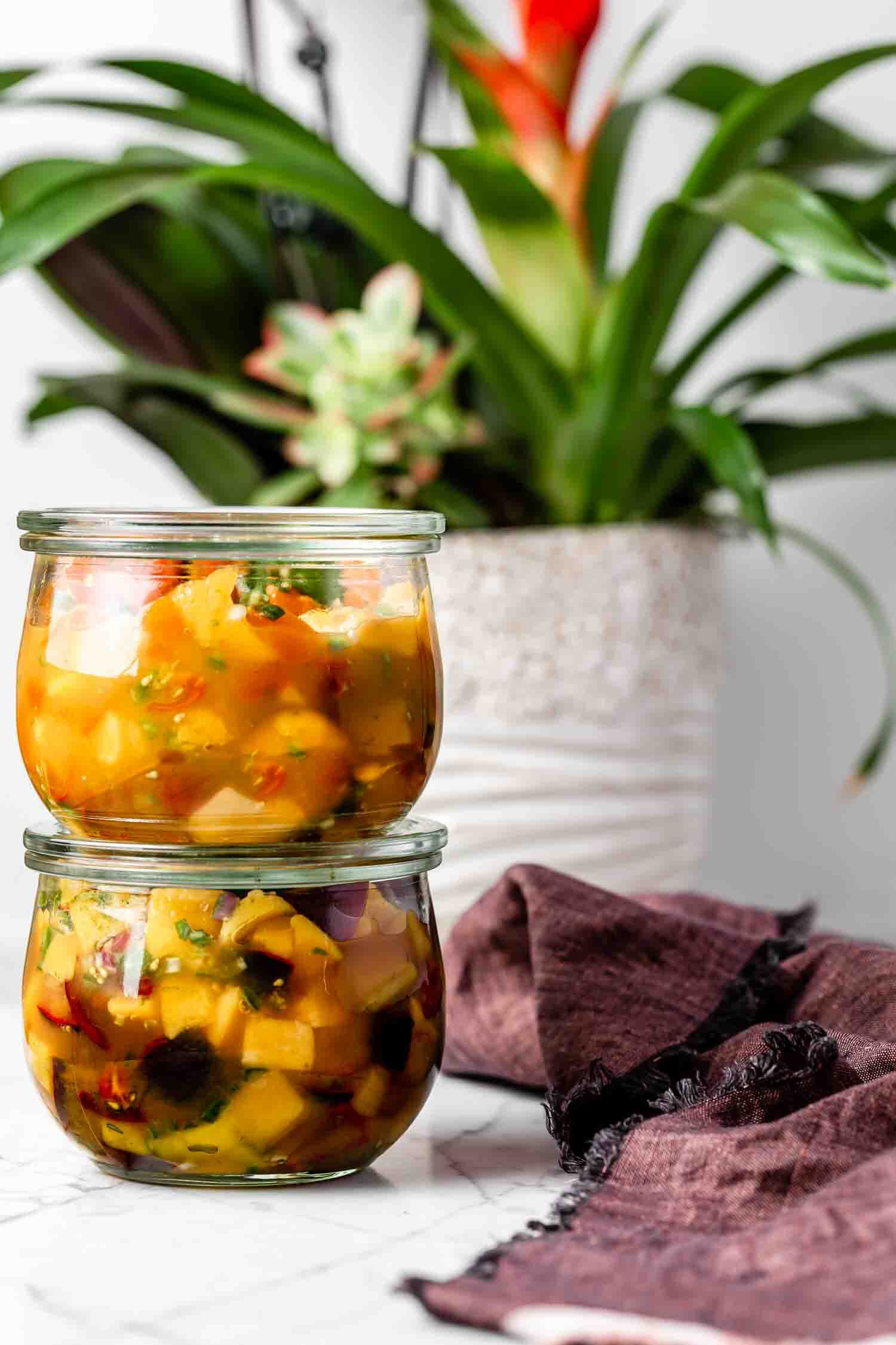 5-ingredient Mango Salsa that is fresh, vibrant, and full of flavor - plus, it's ready in just a few minutes! Sure to disappear quickly, so make a big batch! Recipe by Kari of Beautiful Ingredient. Two jars, each with a different type of cherry tomato.  #mangosalsa #mangorecipe #mangosalsarecipe #vegan #plantbased #salsarecipe #oilfree #glutenfree #sugarfree #easyrecipe #quickandeasyrecipes #quickeasymeals #veganmexicanfood