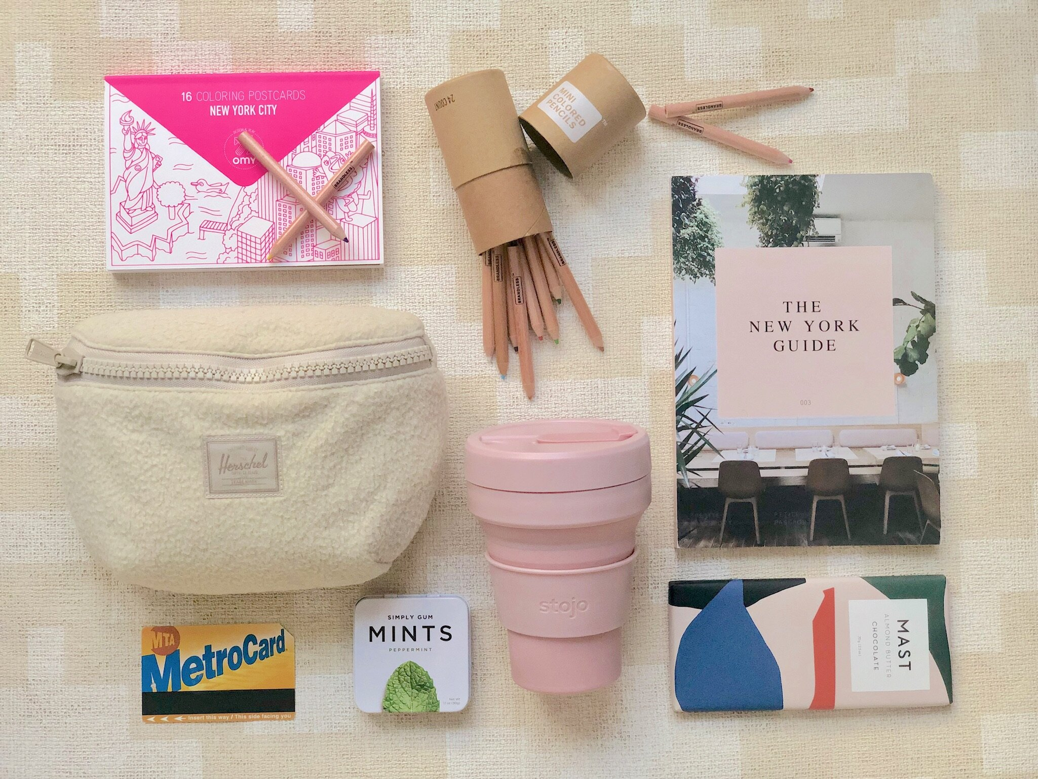 Herschel Supply Co. Fourteen Fanny Pack  ,   OMY New York Coloring Postcards   ,    Brandless Mini Colored Pencils   ,    Stojo 8oz Cup   ,    Petite Passport The New York Guide   ,    Mast Chocolate Bar   ,    Simply Gum Mints   , NYC Metro Card