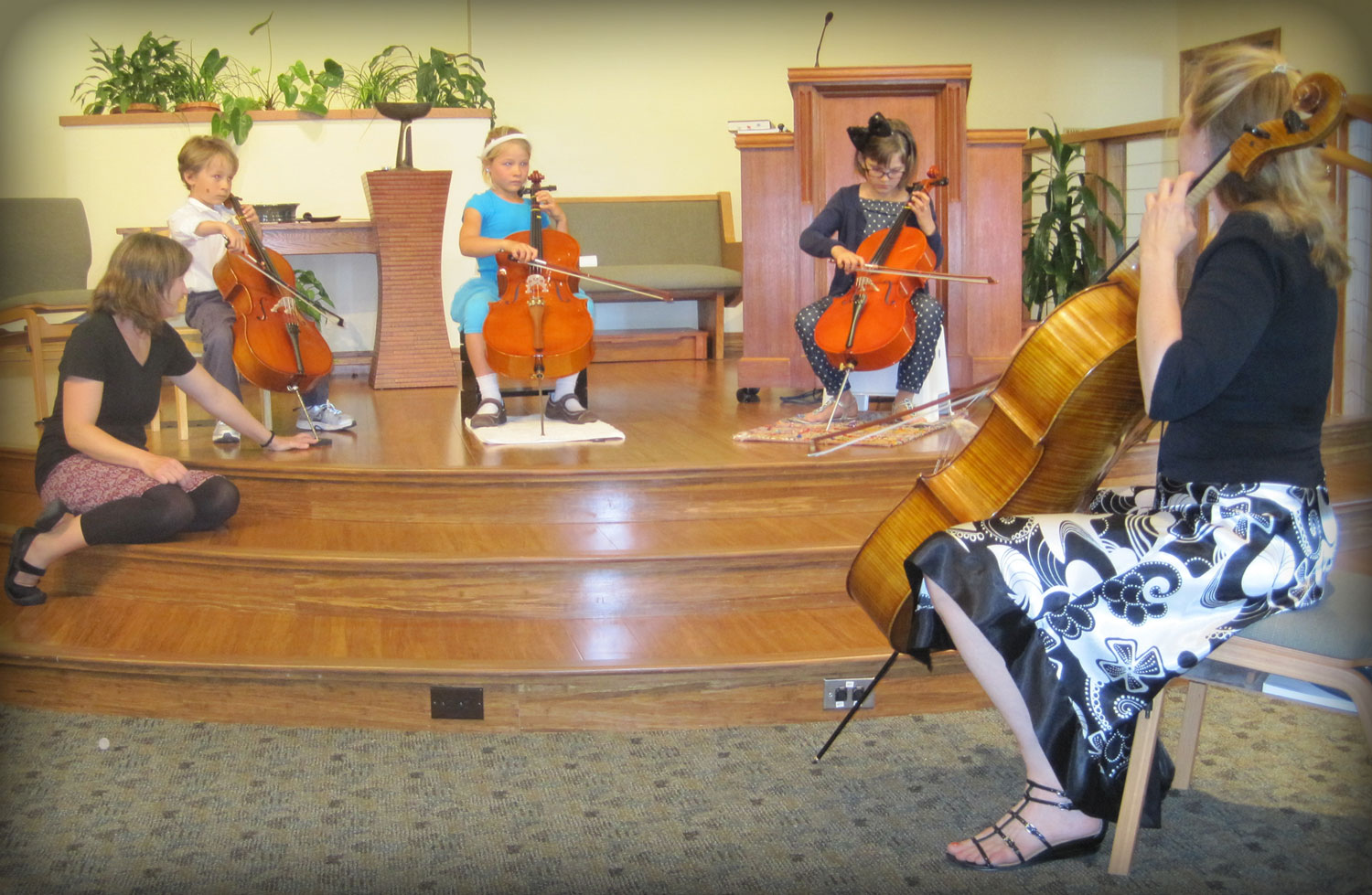 Lynne Oliverius of Encore Strings leads a student concert with some of her young cello students.