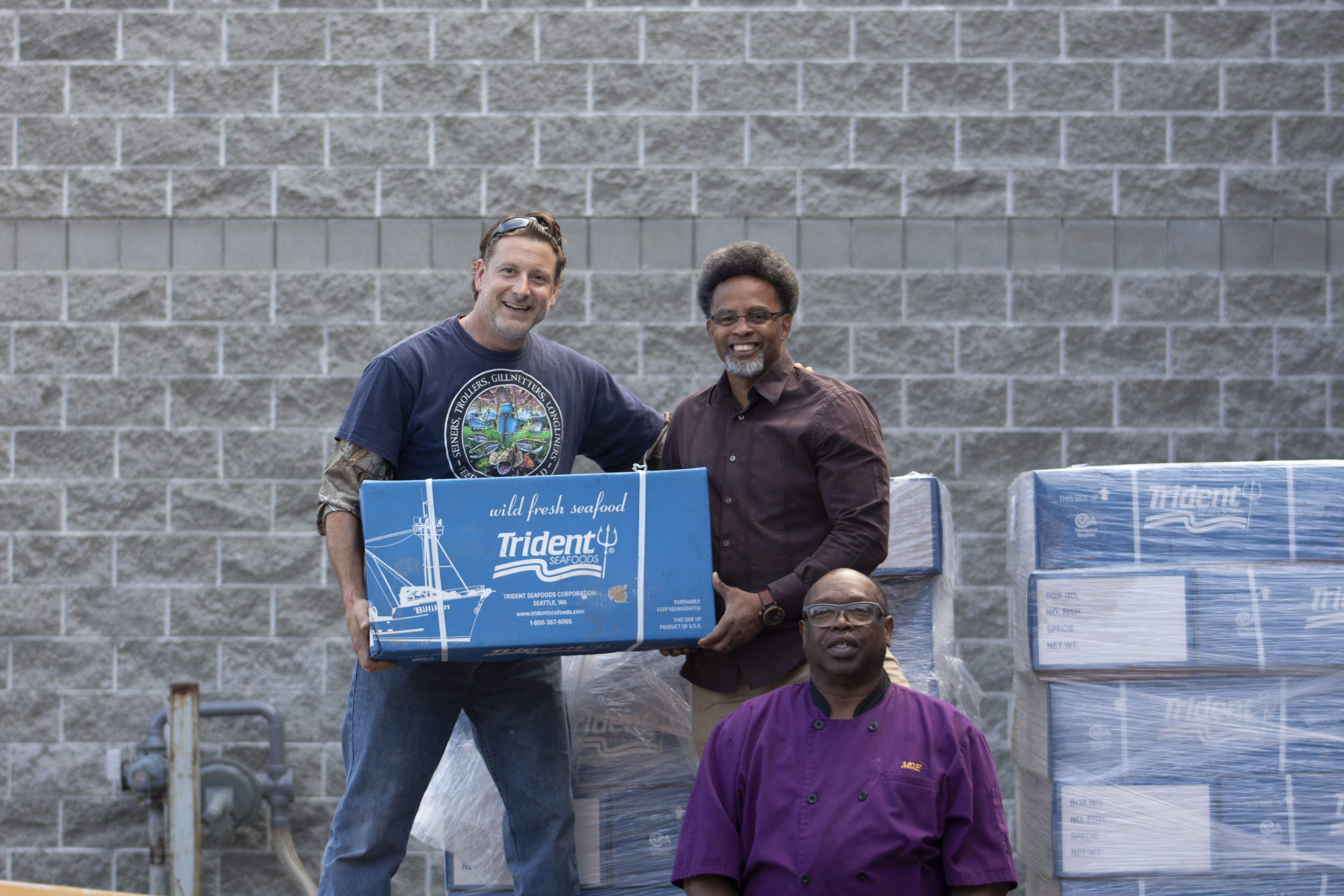 Ryan Talvi (Trokia fishing vessel), Rodney Gaskins (FRM Executive Director) and Moe Mutakabbir (FRM Kitchen Manager) with 2,000 lbs. Sockeye salmon.
