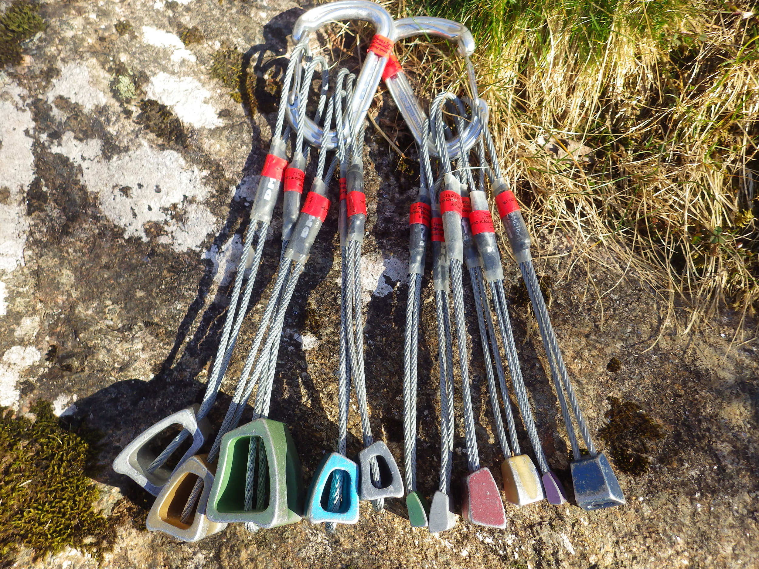 A full set of anodised DMM Walnut wires (1-11), on two seperate wire gate carabiners