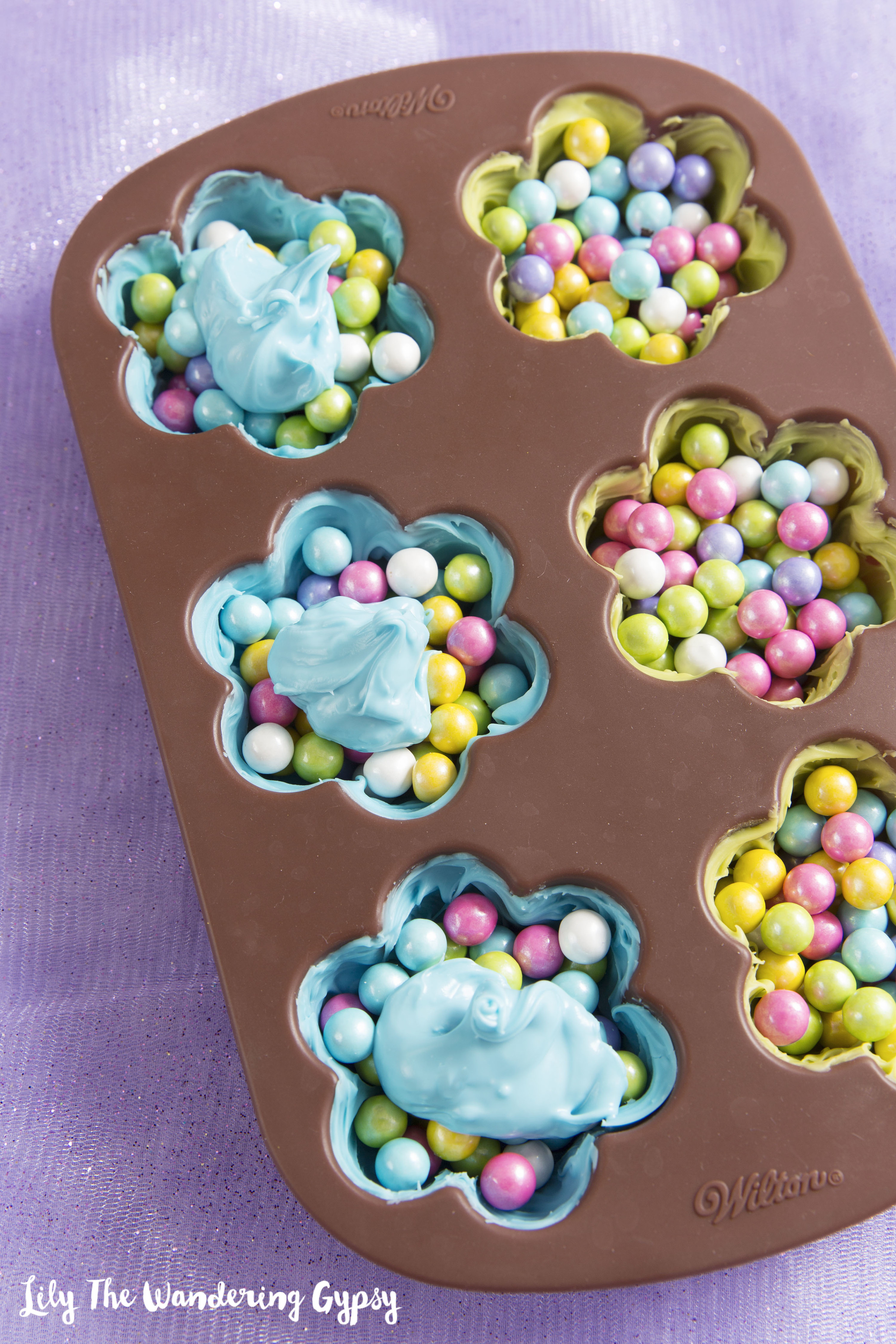 5.) Add a dollop of candy melts on top of your fillers candies, and use the  paintbrush  to smooth the dollop out, and to create a seal, so the candies stay inside the melts. Throw them back into the freezer, and wait about 30 minutes (or longer), so that everything hardens and seals.