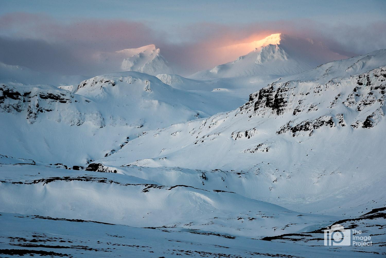 Early morning light catches mountain peaks near Kirkjufell, Iceland