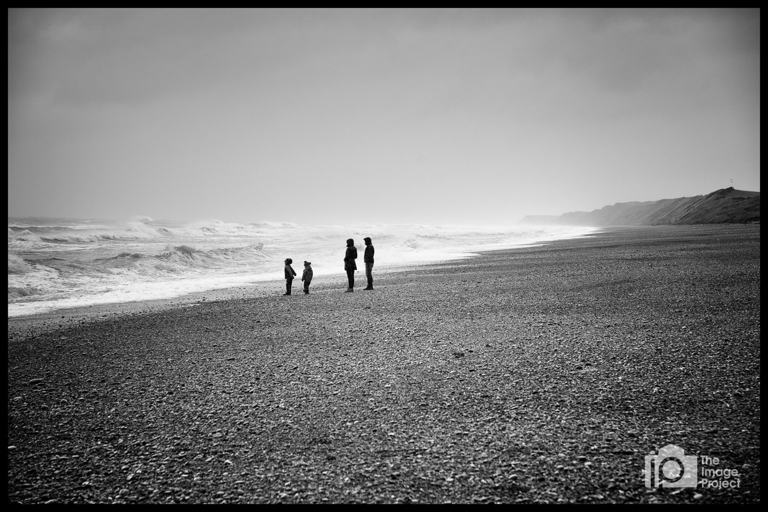 Family walking on beach after storm, Silecroft