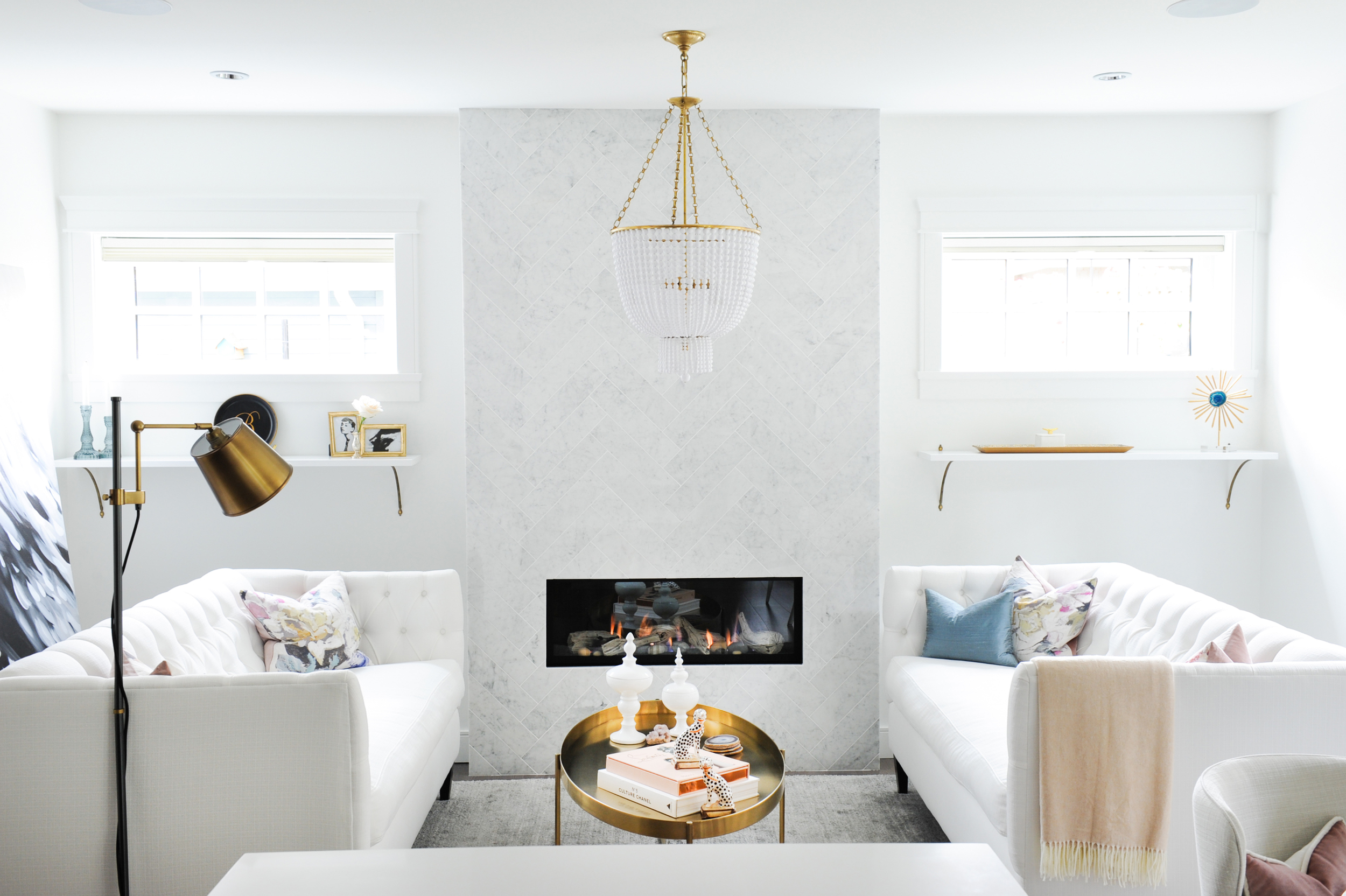 Twin tufted sofas, a chic chandelier and a beautiful marble herringbone fireplace.