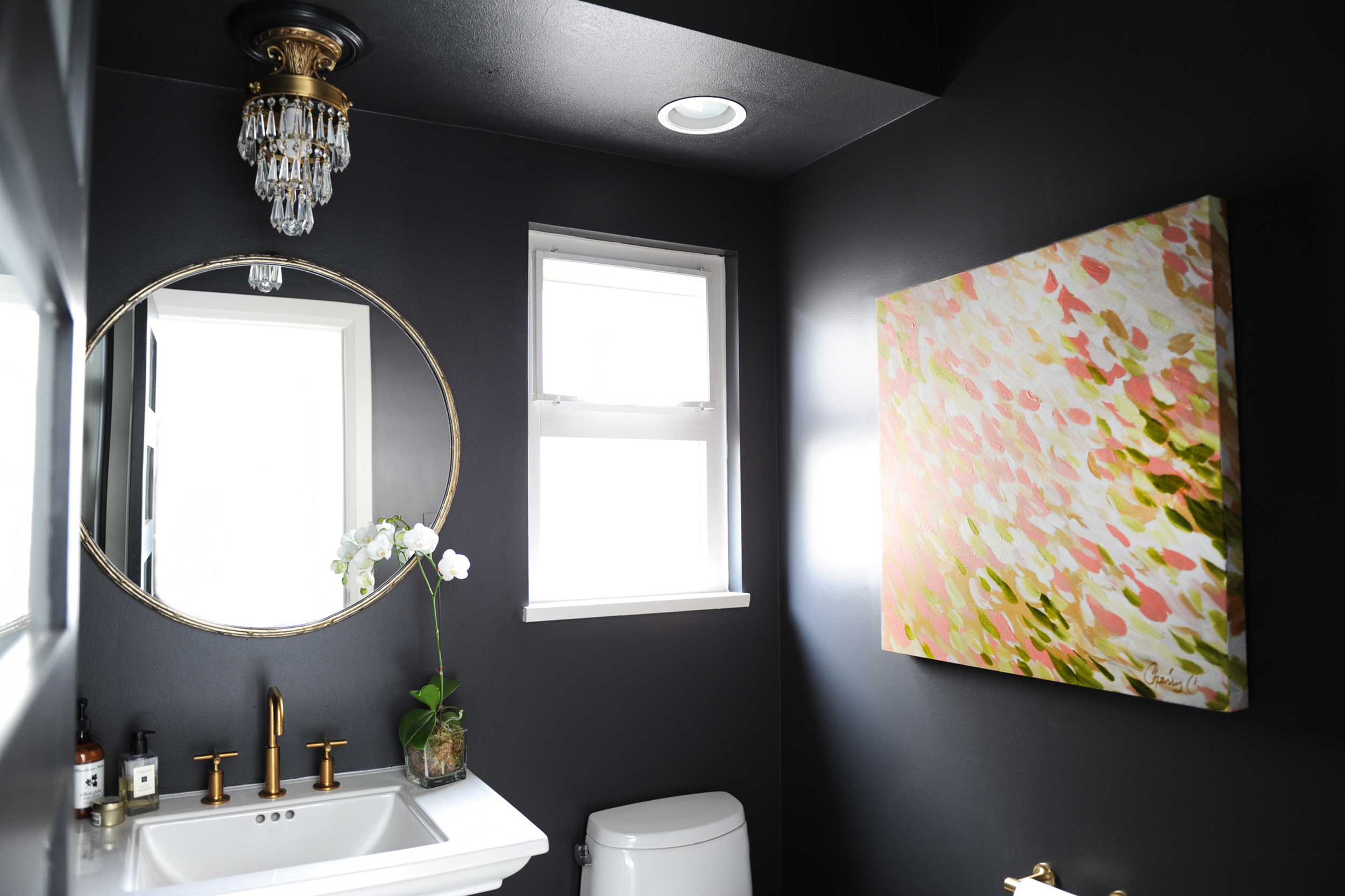 The black walls with the gold fixtures really make this space so timeless and elegant.