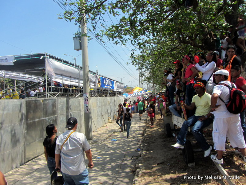 People attempting to watch the main Barranquilla carnival parade from outside of the barricades and bleachers.