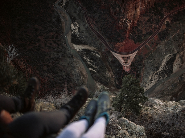 Couple's feet hanging off the edge of Angel's Landing in Zion National Park