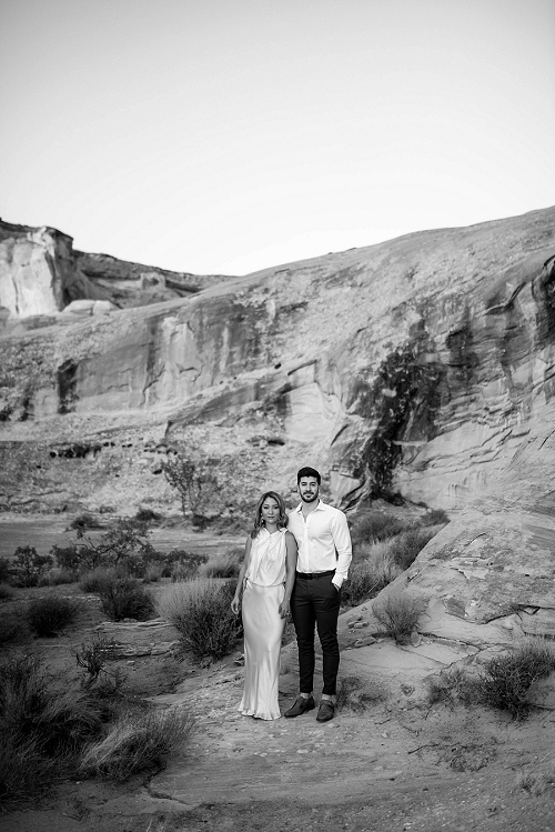 Couple stands near sandstone in Utah desert