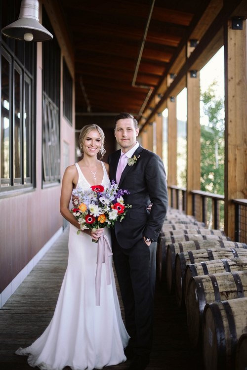 Bride wearing dress with 70's flowers and groom at whiskey distillery wedding