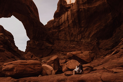 Couple engagement shoot under arch in Moab Utah