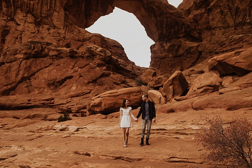Couple walks under double arch in Moab, Utah