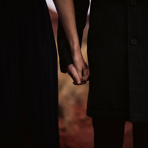 Couple holds hands at engagement shoot in Moab, Utah