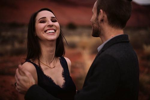 Couple laughing at engagement shoot in Moab Utah
