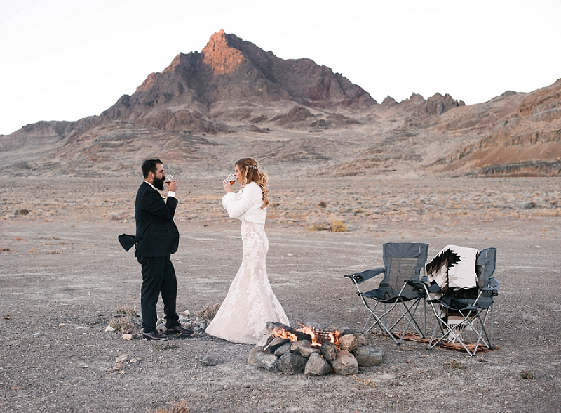 Couple enjoys campfire at sunset at their Utah desert elopement
