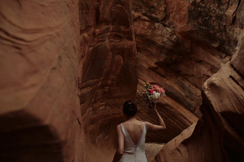 Bride walks thorough slot canyon near Moab Utah