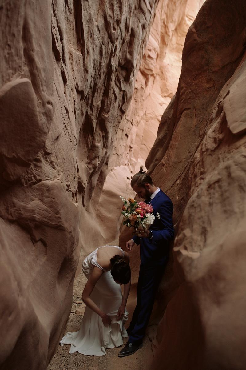 Bride fixes dress at her elopement near Moab Utah