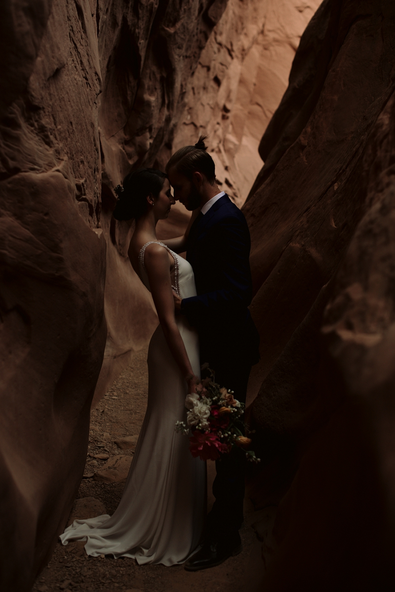 Couple stands in slot canyon at their elopement near Moab Utah