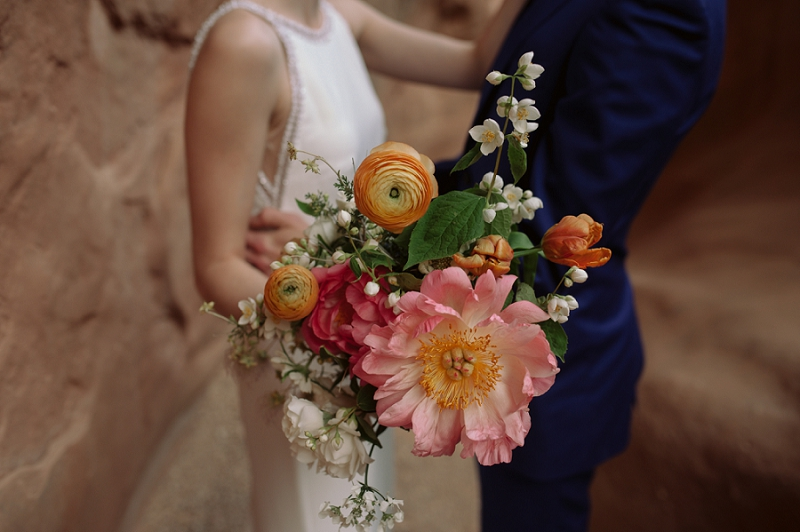 Bride holds wedding bouquet made of sustainable flowers by Beehive Floral Co