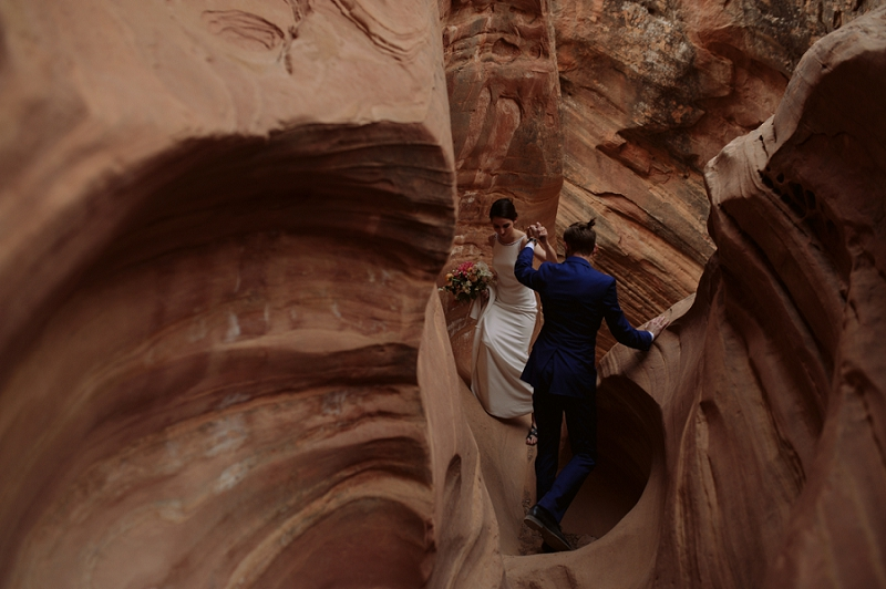 Groom helps bride through slot canyon in Utah's desert