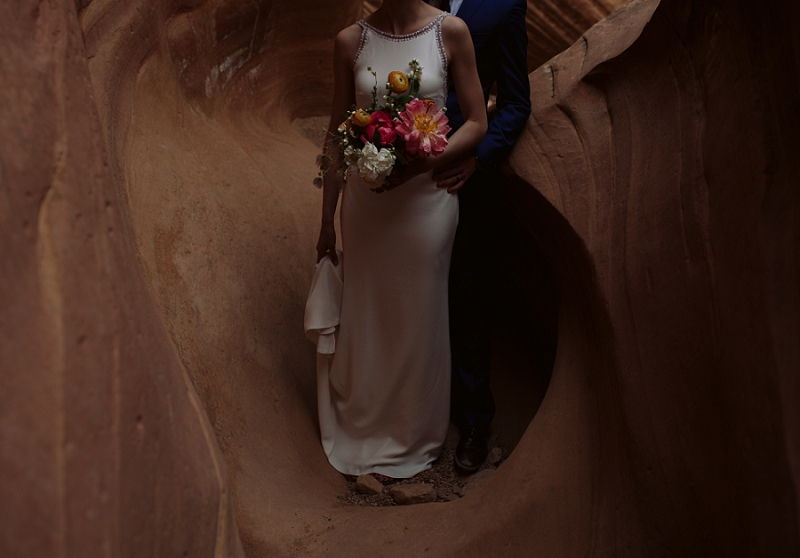Bride holds flowers in slot canyon