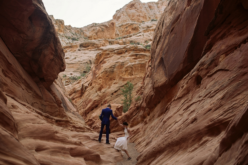Groom helps bride up onto rock in a slot canyon
