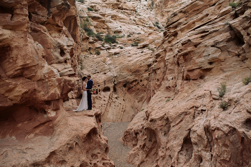 Couple stands on ledge in slot canyon near Moab Utah