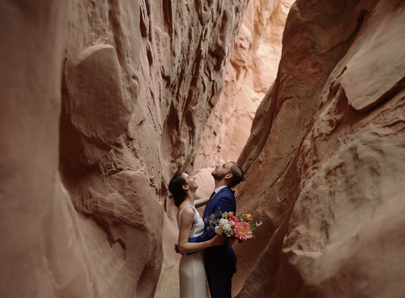 Elopement couple looks up at slot canyon near Moab Utah